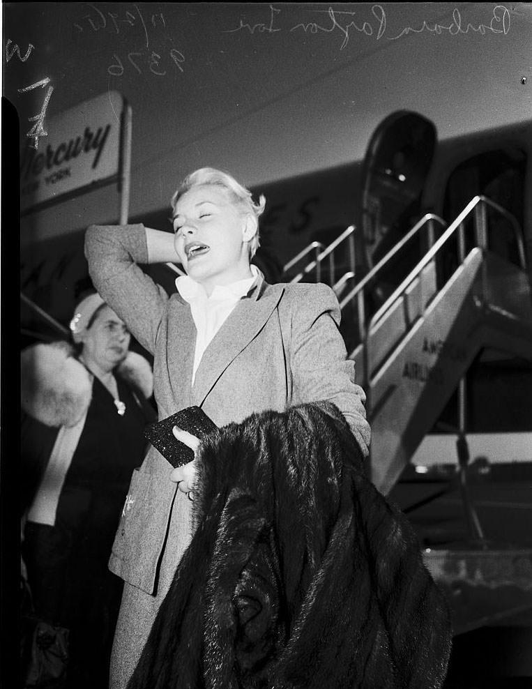 Barbara Payton waiting for the arrival of Franchot Tone, 1951.