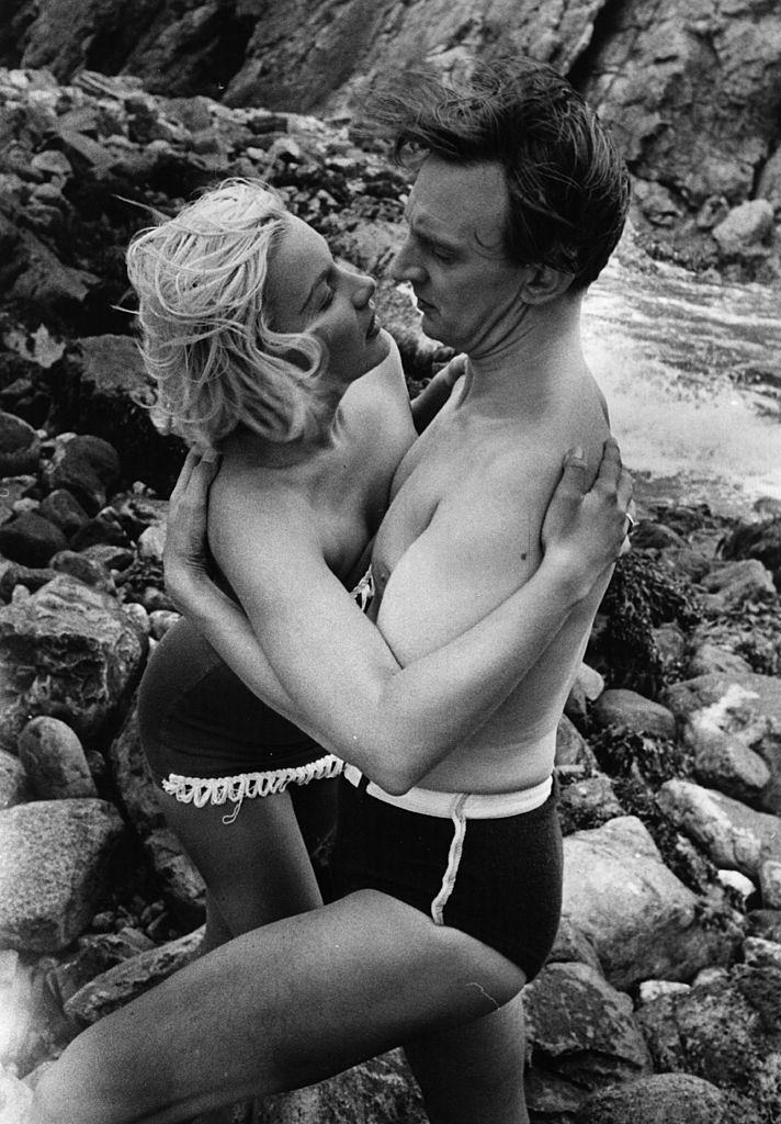 Barbara Payton with Stephen Murray on the beach during the filming of 'The Four Sided Triangle' , 1952.