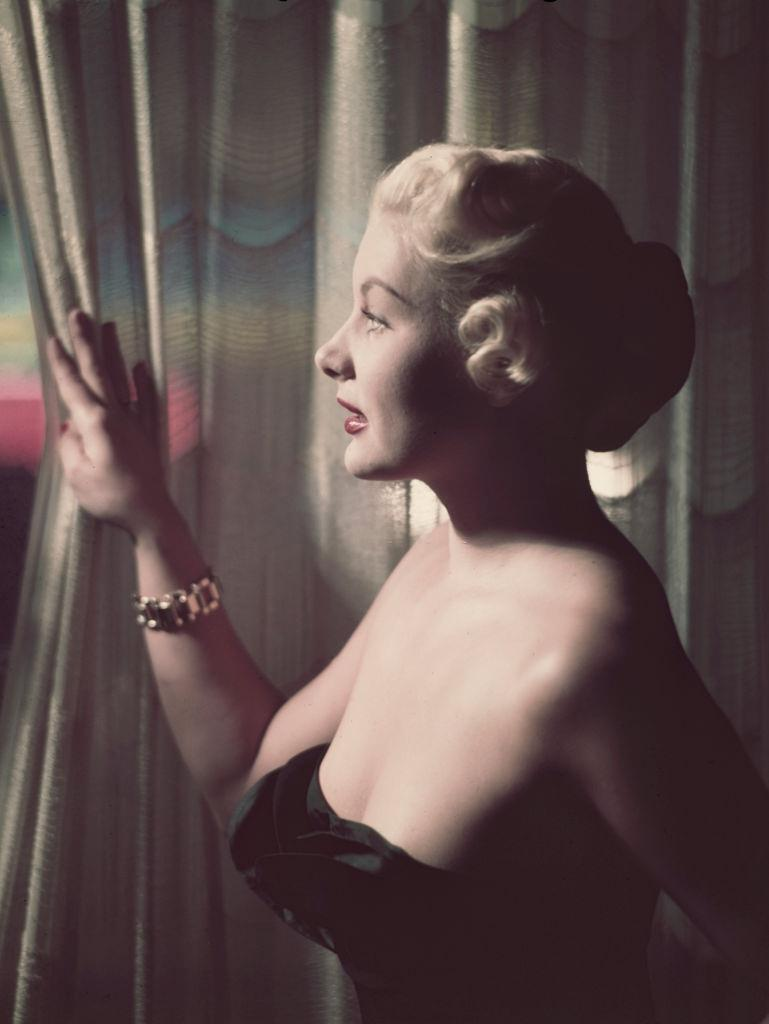 Barbara Payton posed by a curtain in October 1952.