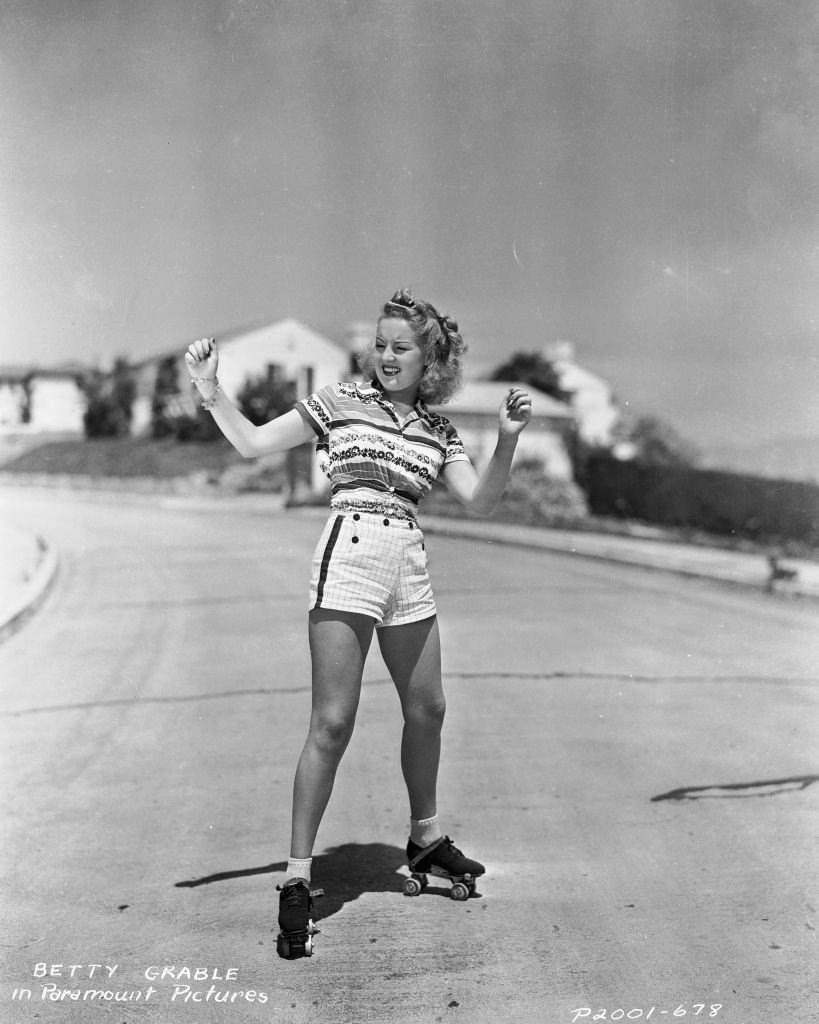 Betty Grable balancing on a pair of roller skates, 1935.
