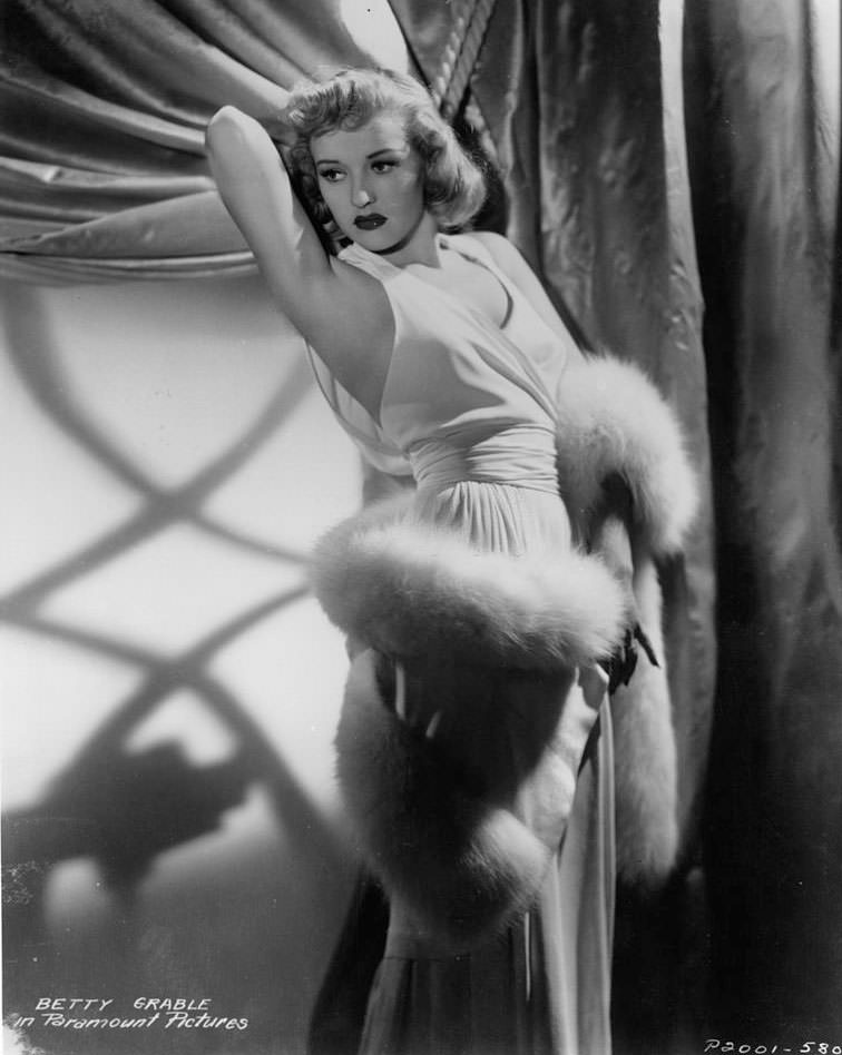 Betty Grable in an evening gown and a white fur wrapped around her body, 1935.