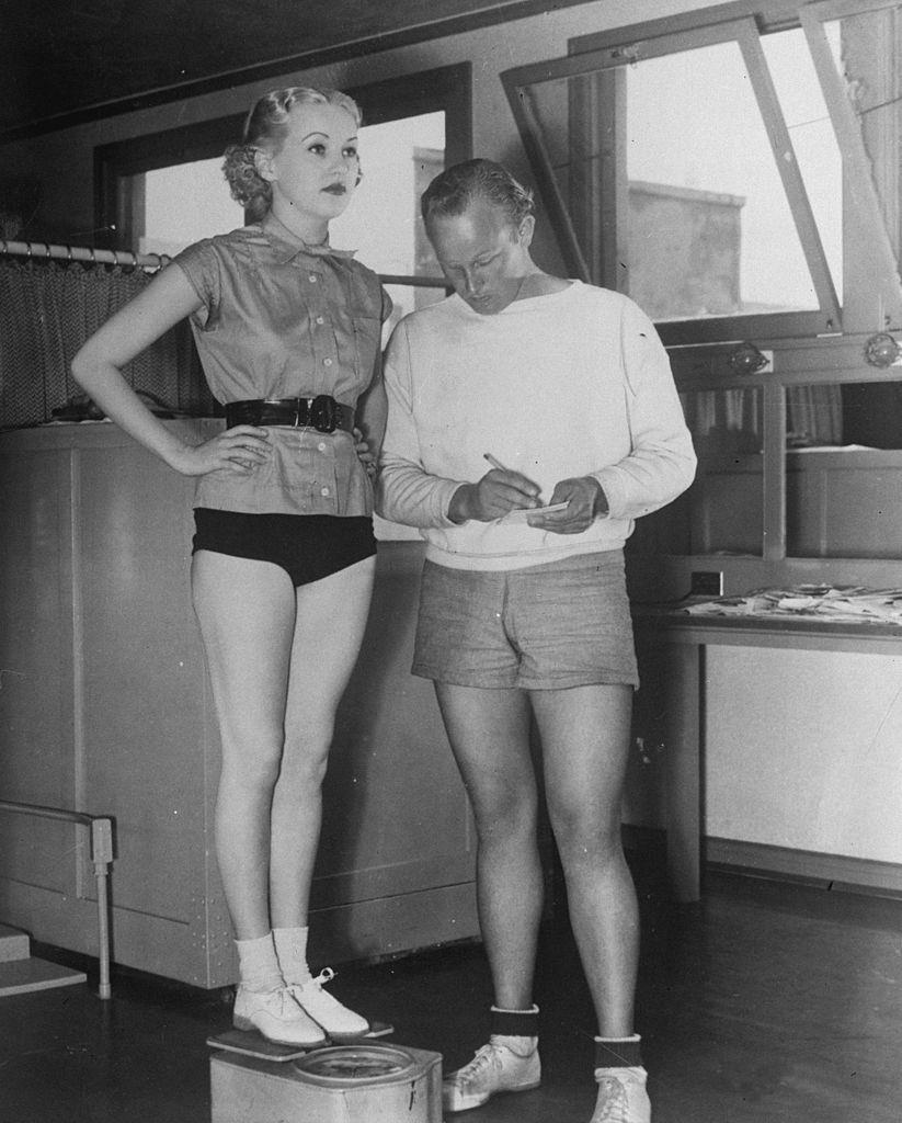 Betty Grable is weighed by her personal trainer, 1936.