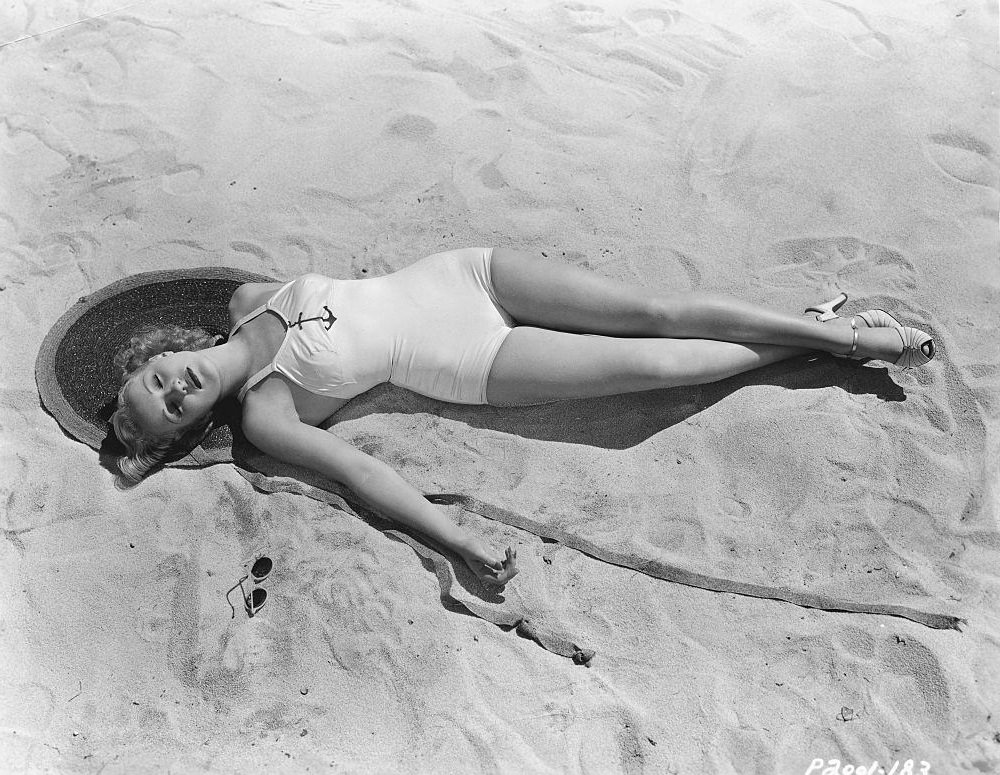 Betty Grable relaxing on the beach, 1937.