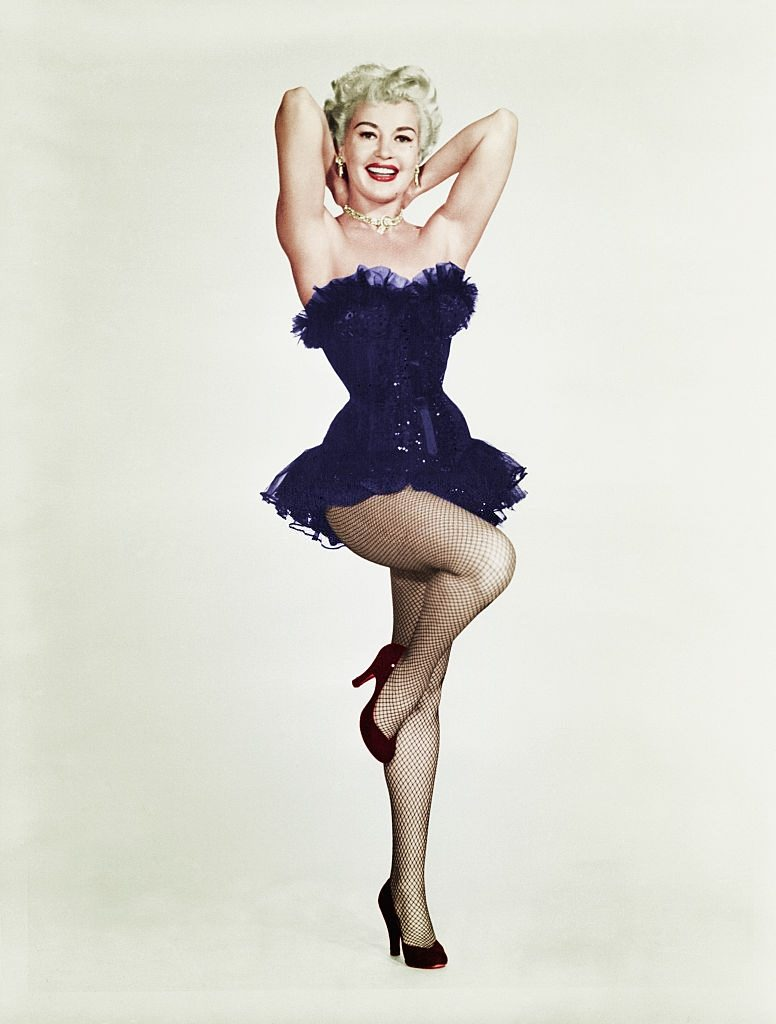 Betty Grable posing with one leg up and arms behind her head, 1950s.