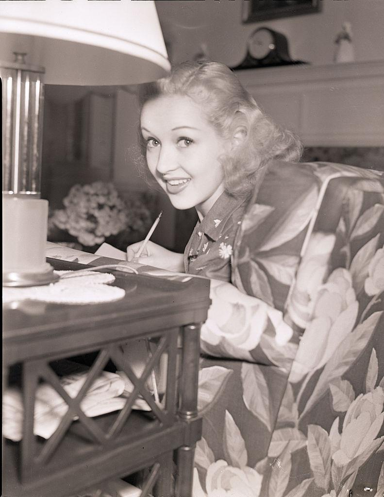 Betty Grable, smiling at the camera while seated and writing in a chair, 1939.