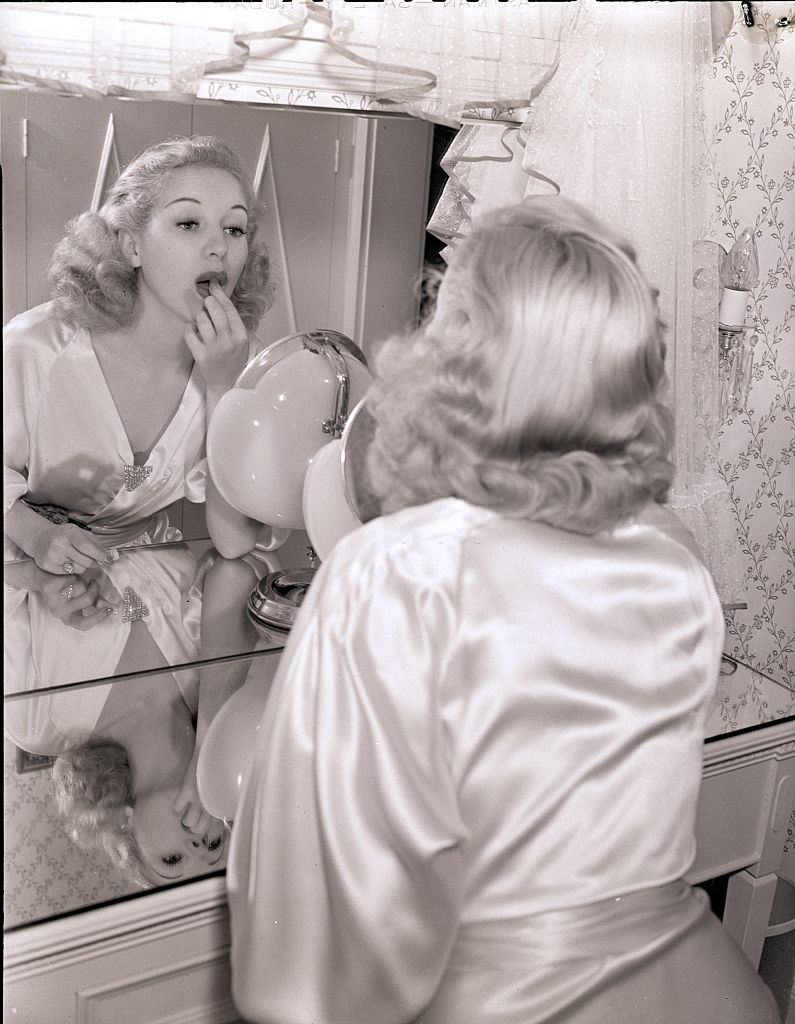 Bertty Grable, wearing a satin robe and applying lipstick in a mirror, 1939.