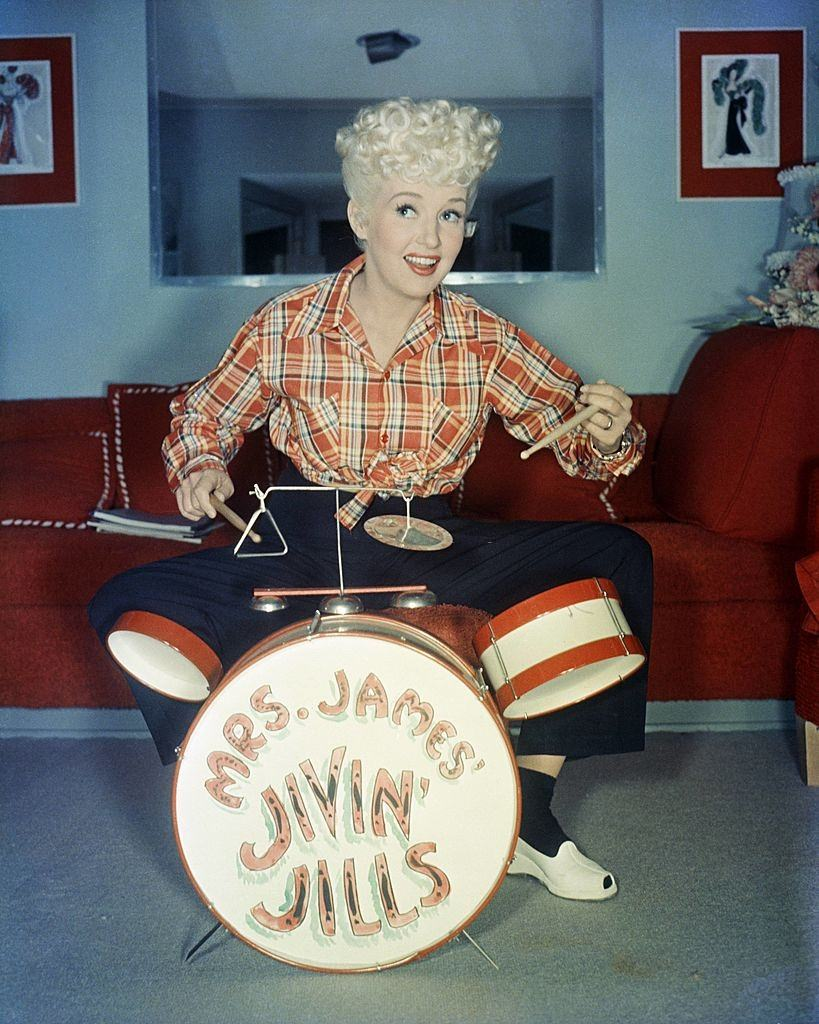 Betty Grable wearing a plaid shirt, sitting behind a child's drum kit, which has 'Mrs James Jivin' Jills', 1940.