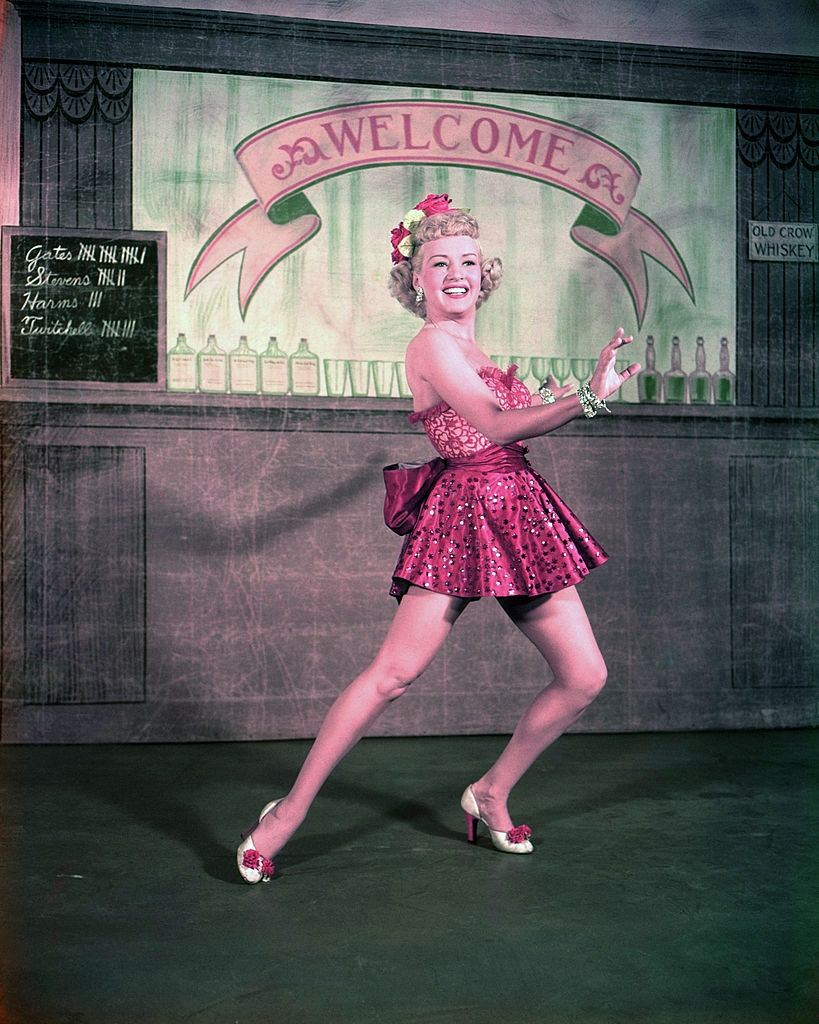 Betty Grable wearing a short red dress as she holds a dance pose, 1940.