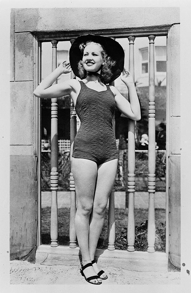 Betty Grable poses in a swim suit and hat, 1940.