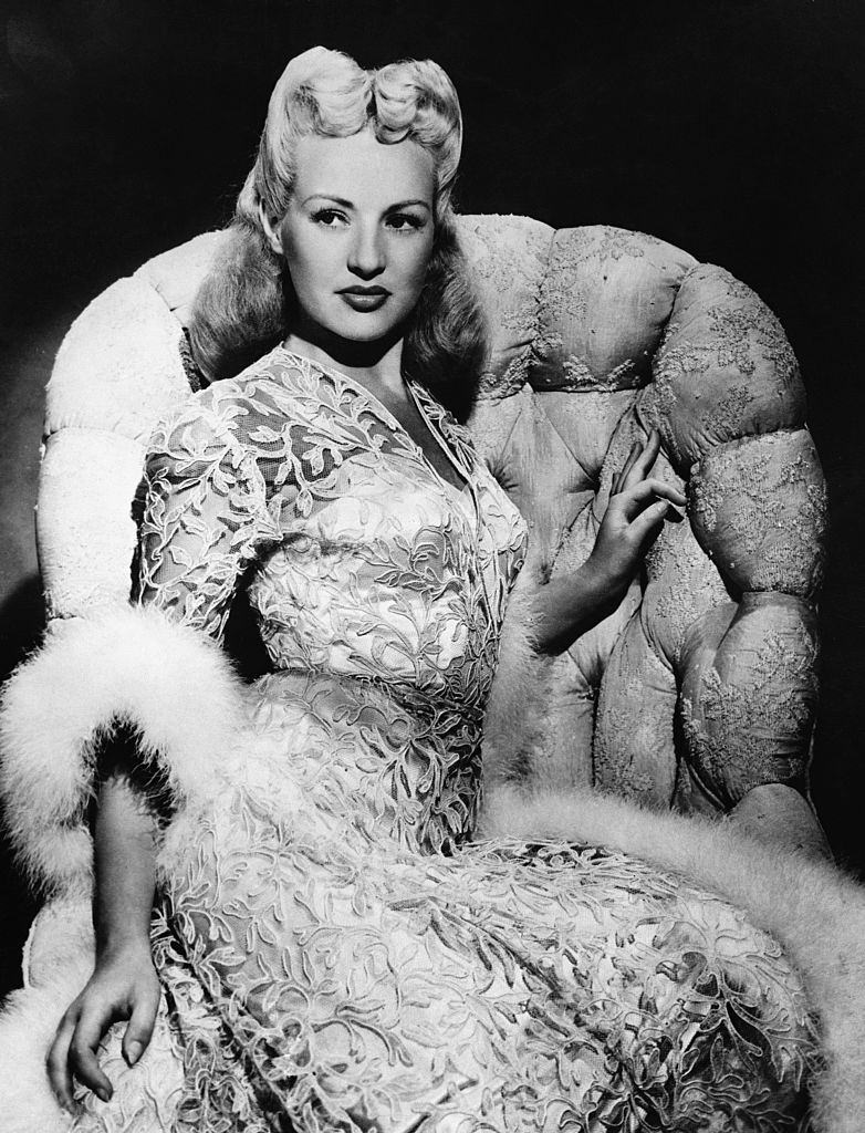 Betty Grable posing on the sofa, 1944.