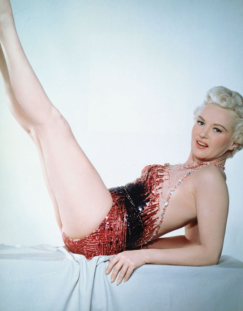 Betty Grable poses wearing a red-and-black bodice as she leans back with her legs legs in the air at an angle, 1940.