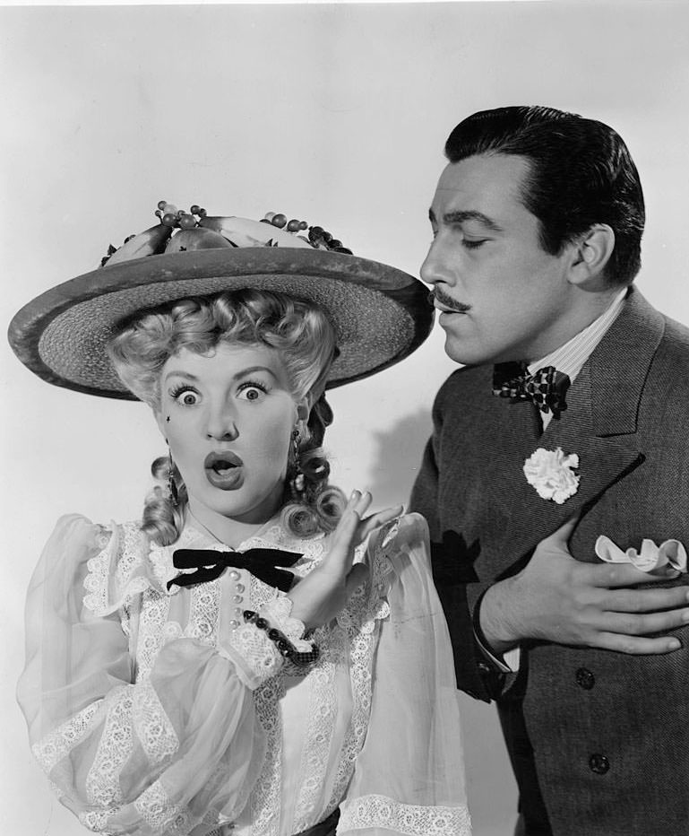 Betty Grable puts her hand up as Cesar Romero holds his heart in a scene from the film 'Coney Island', 1943.