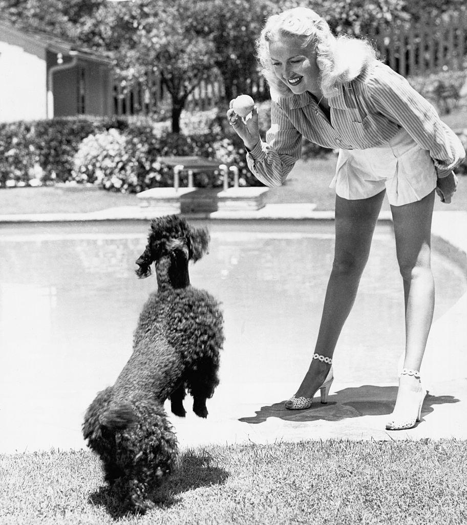Betty Grable Playing with her Poodle, 1944.