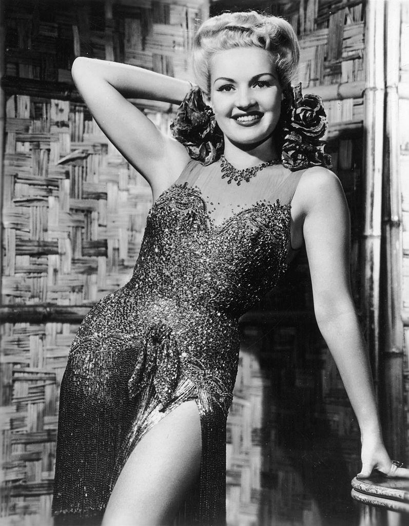 Betty Grable posing in a slit sequined dress, 1945.