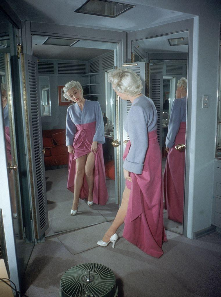 Betty Grable lifts her robe to look at her legs in a mirror, 1950.