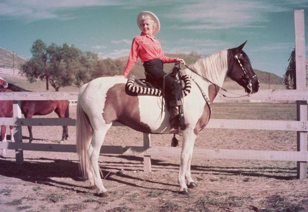 Betty Grable squinting in the sun while seated on a pinto horse with brown patches in a corral, 1952.