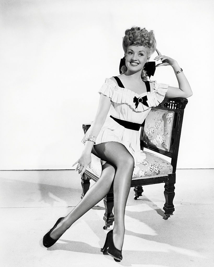 Betty Grable wearing a short, white, pleated dress, 1945.
