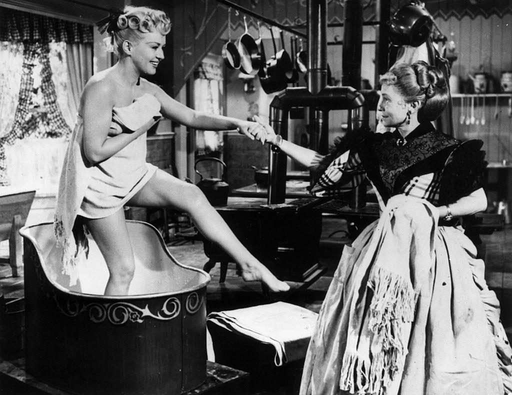 Betty Grable steps out of a wash basin wearing a towel, while Thelma Ritter holds her hand to give her support, 1953.