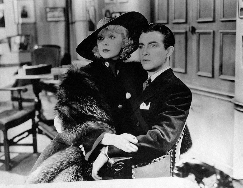 Eleanor Powell, terrified, sits on Robert Taylor's lap in the movie 'Broadway Melody of 1938'.