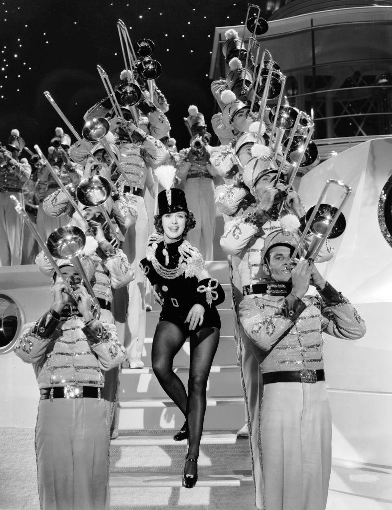 Eleanor Powell descends a staircase lined with trombone players in the musical 'Born To Dance', 1936.