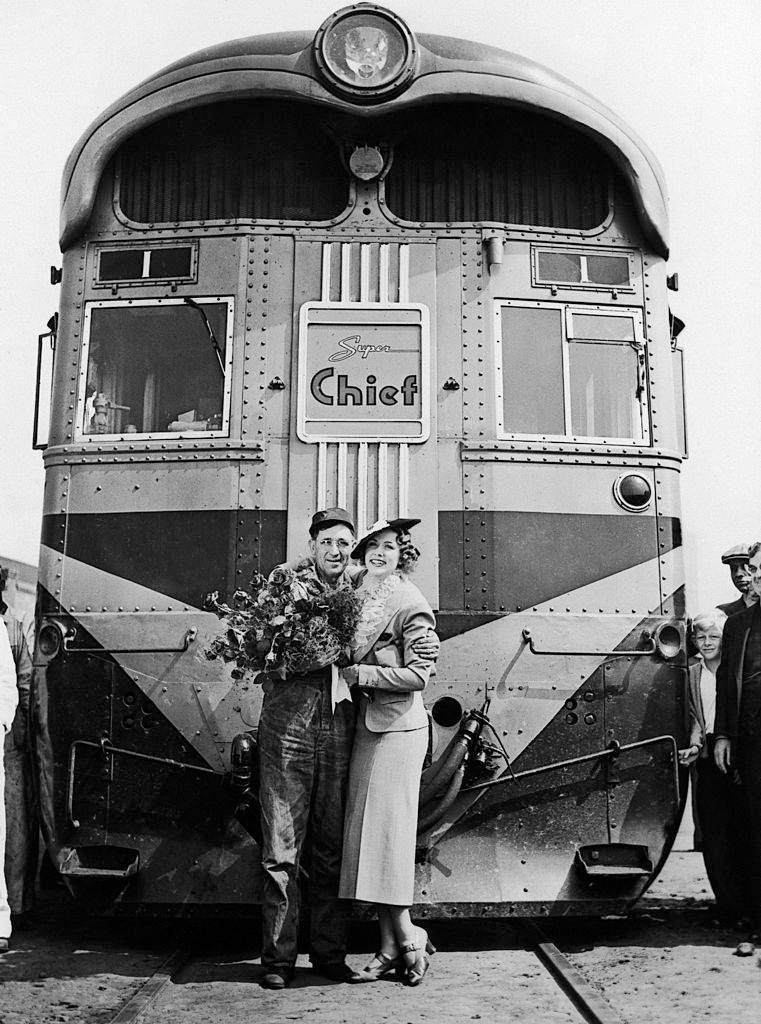 Eleanor Powell arrives in Los Angeles, California aboard The Express Train Super Chief and posing with the Driver, 1936.