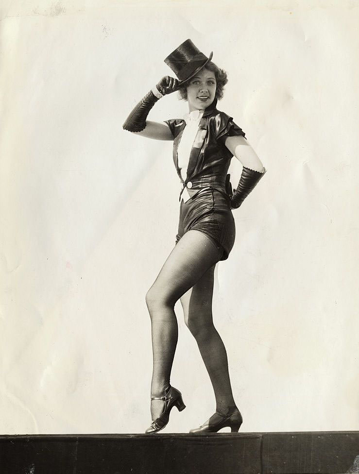Eleanor Powell finishes her 'warmin' up' routine by strutting off the stage with a quizzical look.