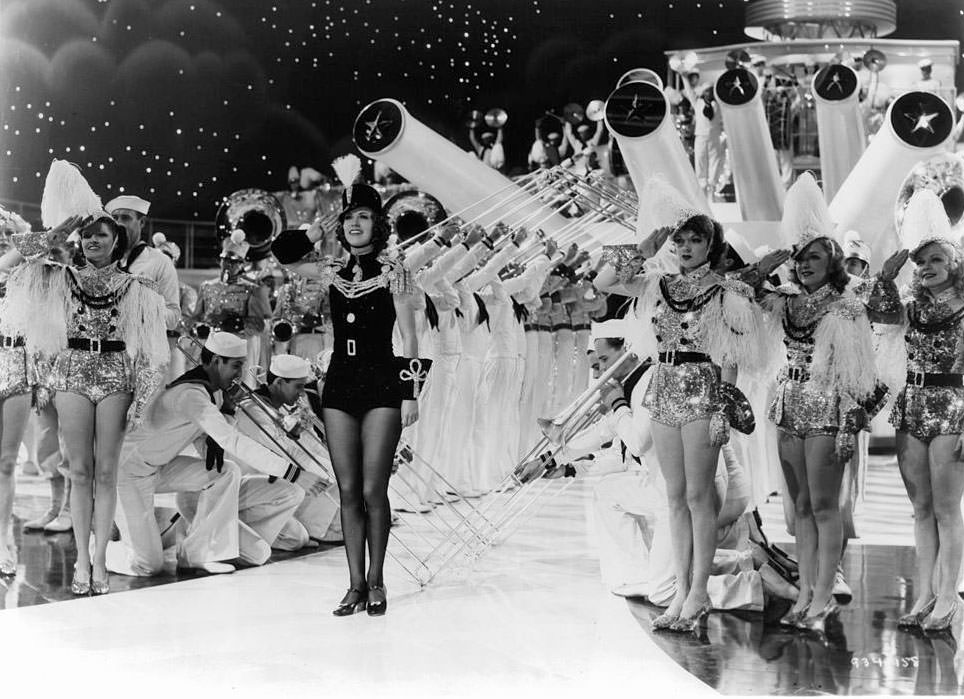 Eleanor Powell gives a salute with many other performers in a scene from the film 'Born To Dance', 1936.