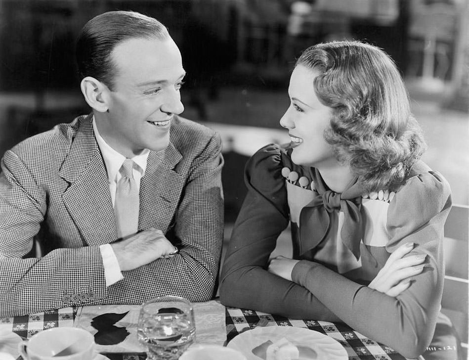 Eleanor Powell and Fred Astair share a smile at the table in a scene from the film 'Broadway Melody Of 1940',