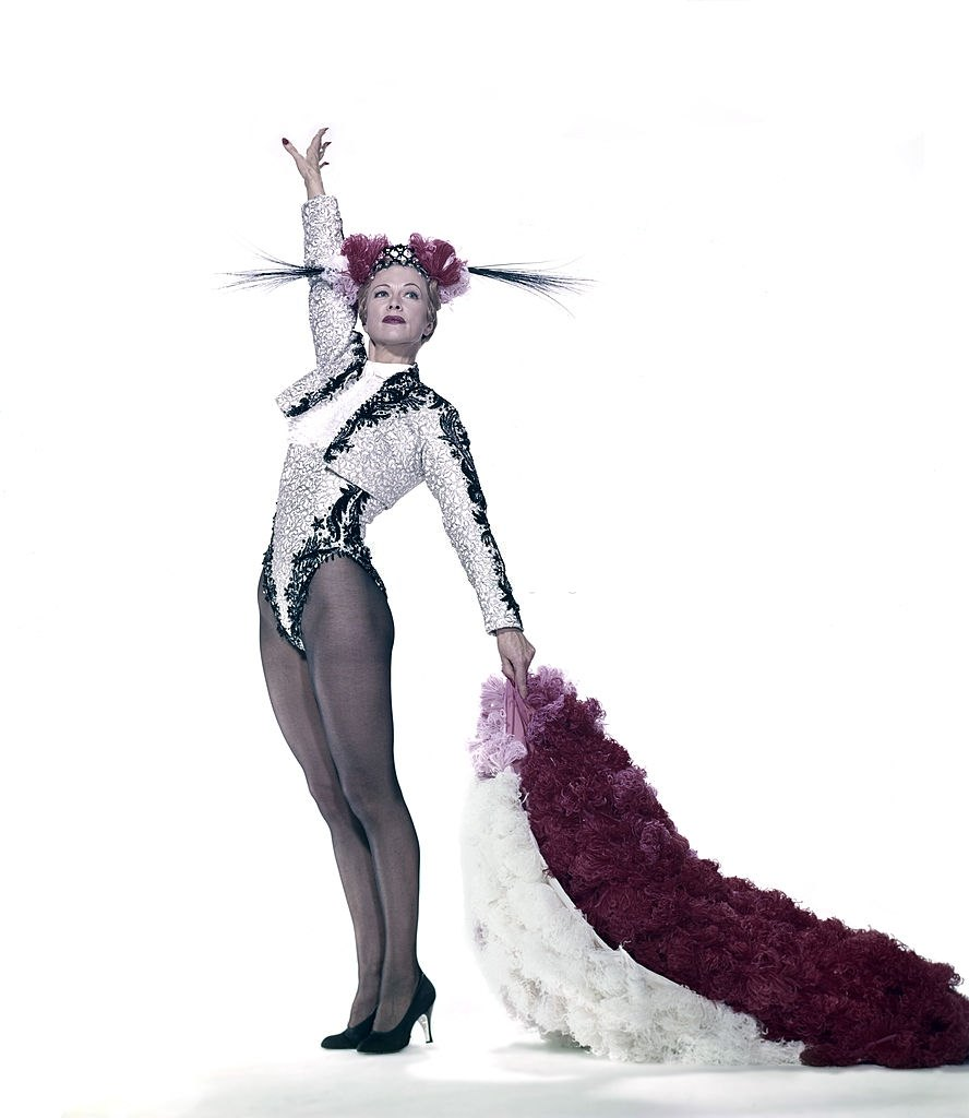 Eleanor Powell in a customized matador's costume, raises her right arm high in the air and holds a red and white feathered cape, 1955.
