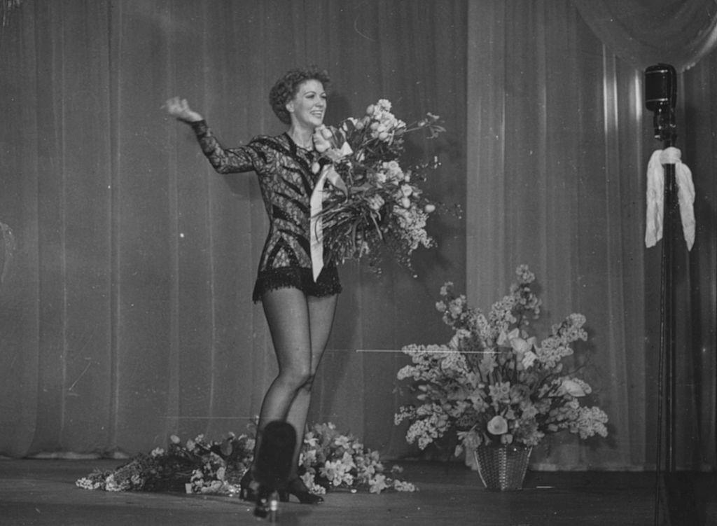 Eleanor Powell holding a bouquet of flowers following a performance on the stage, March 21st 1949.