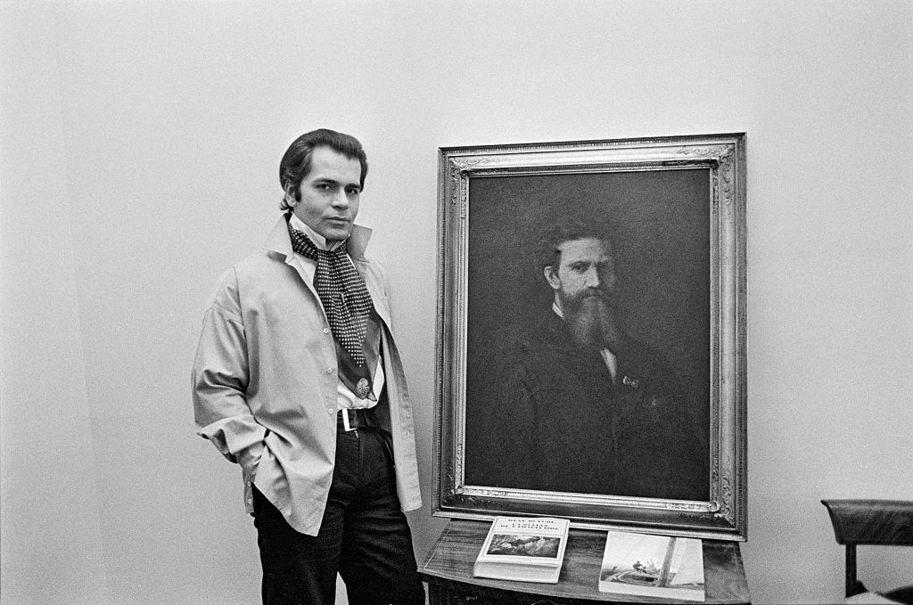 Karl Lagerfeld posing with a painting, 1976.