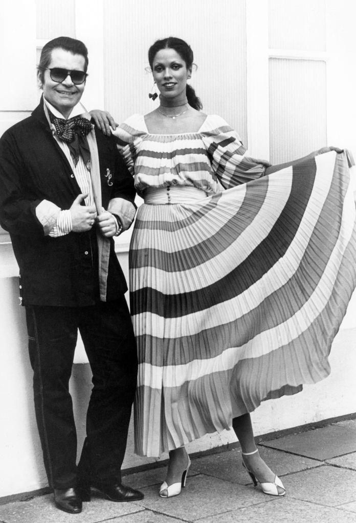 Karl Lagerfeld next to a model in a pleated dress from Lagerfeld's Chloe collection, 1977.