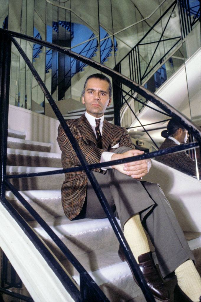 Karl Lagerfeld, posing on the steps of the Chanel store, 1983.