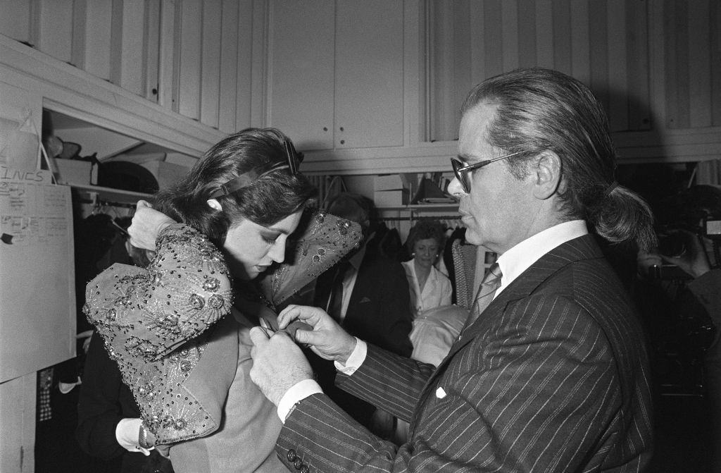 Karl Lagerfeld with a model ahead of the presentation of spring-summer haute couture collection for Chanel in Paris, 1983.