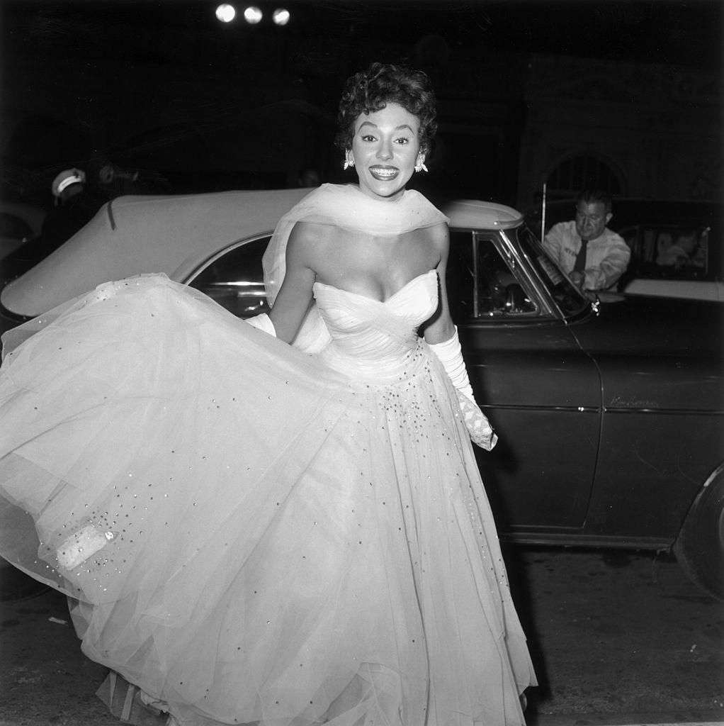 Rita Moreno warnig a white evening gown and arriving at the premiere of director Charles Walters' film 'Lili', 1953.