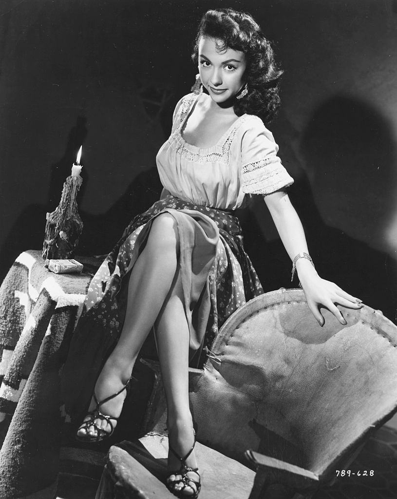 Rita Moreno, sitting on a table with her feet on a chair, as she appears in the movie 'Cattle Town', 1952.