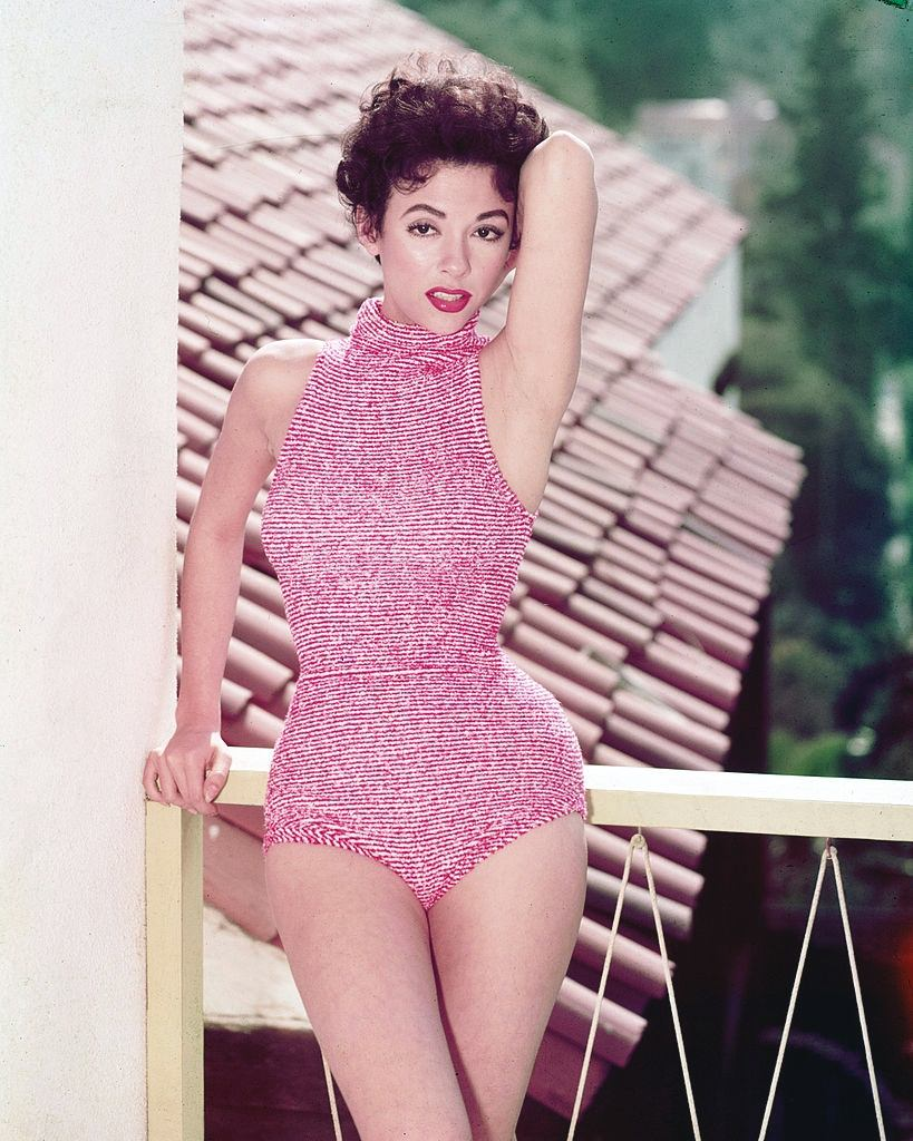 Rita Moreno wearing a red-and-white halterneck swimsuit, posing on a balcony overlooking a rooftop, 1955.