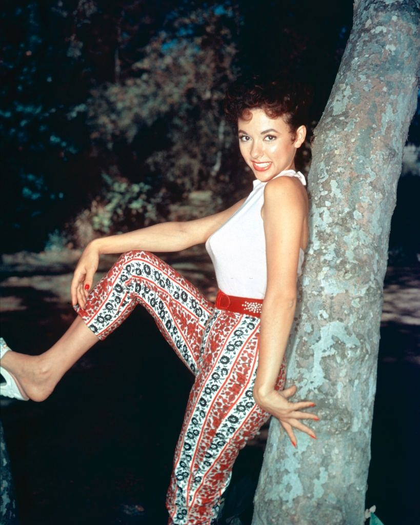 Rita Moreno posing while leaning by a tree, 1955.