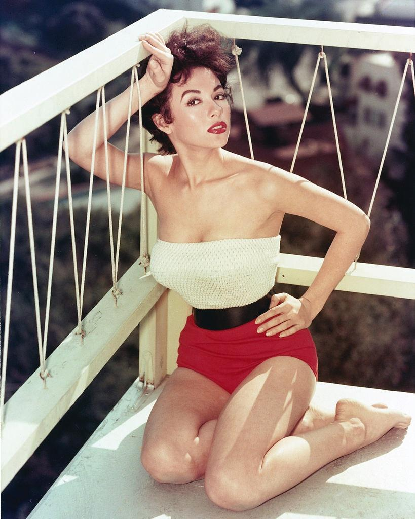 Rita Moreno in white top and red shorts, 1955.