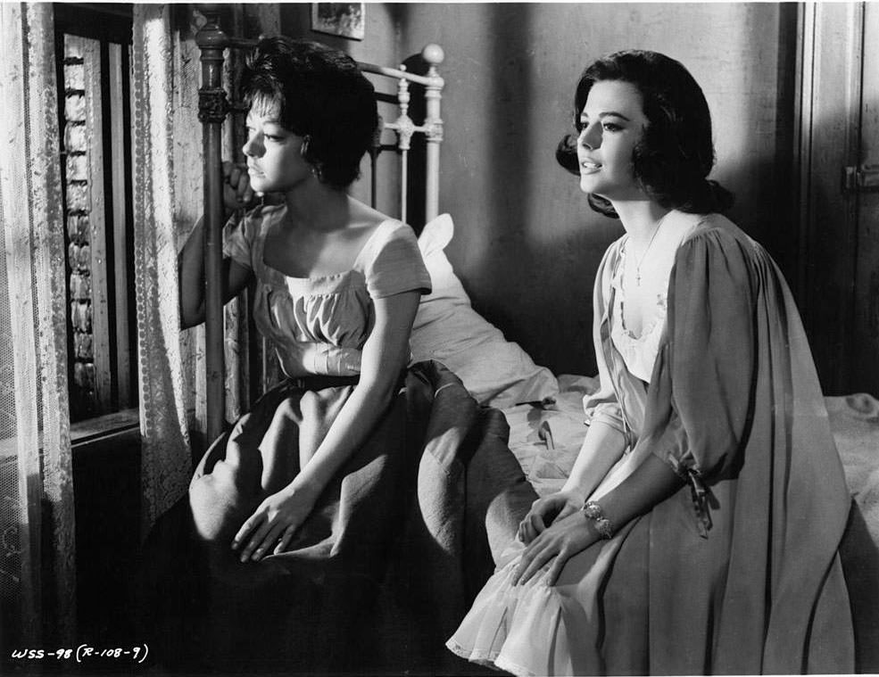 Rita Moreno and Natalie Wood sitting on a bed looking out of a window together in a scene from the film 'West Side Story', 1961.