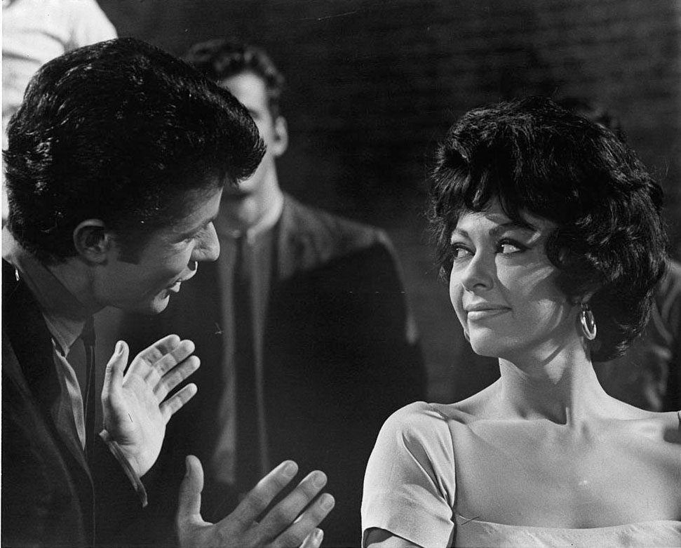 Rita Moreno listens while George Chakiris speaks with her in a scene from the film 'West Side Story', 1961.