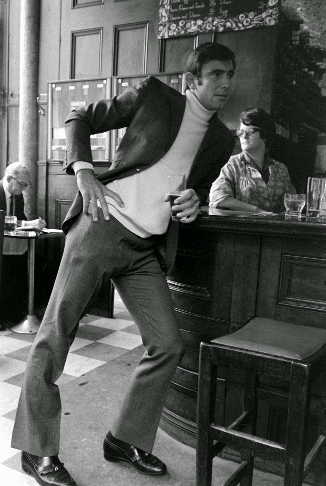 George Lazenby leans against a bar during a moment away from James Bond auditions, 1967.