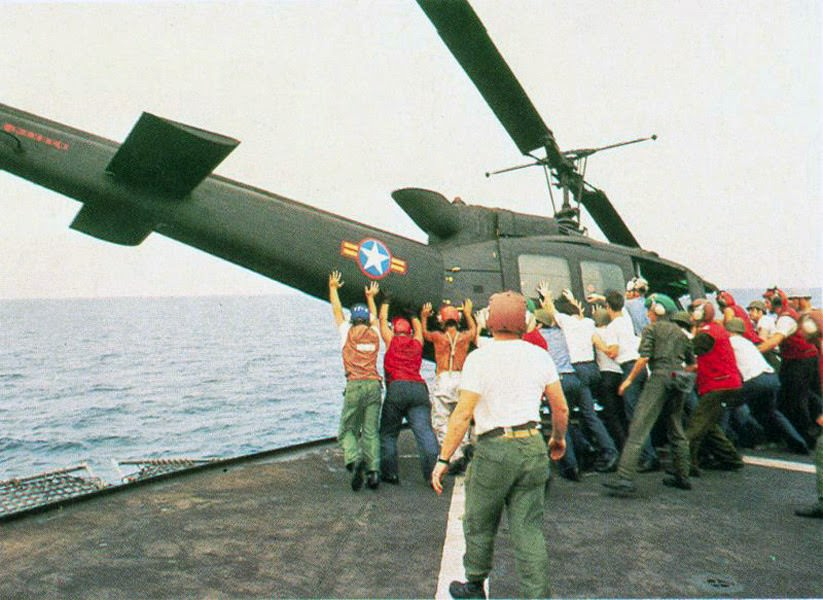 Japan ESouth Vietnamese UH-1H being pushed overboard to make room for a Cessna O-1 landing.