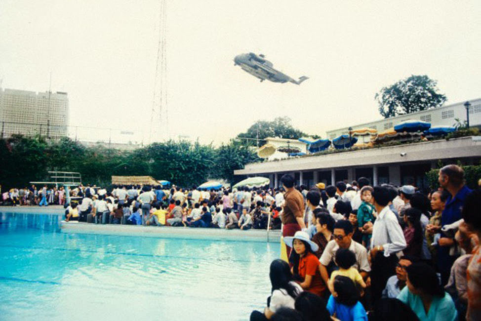 Crowds of Vietnamese and Western evacuees wait around the swimming pool inside the American Embassy compound in Saigon hoping to escape Vietnam via helicopter before the arrival of North Vietnamese troops.