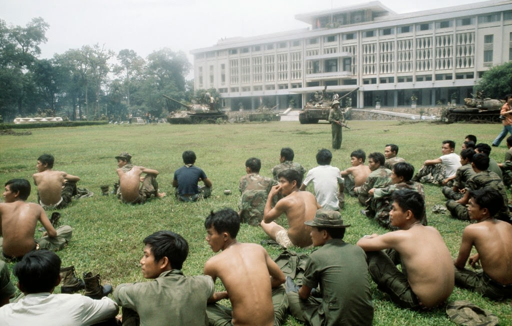 Captured South Vietnamese soldiers sit on a broad lawn after North Vietnamese troops seize the presidential palace in Saigon.