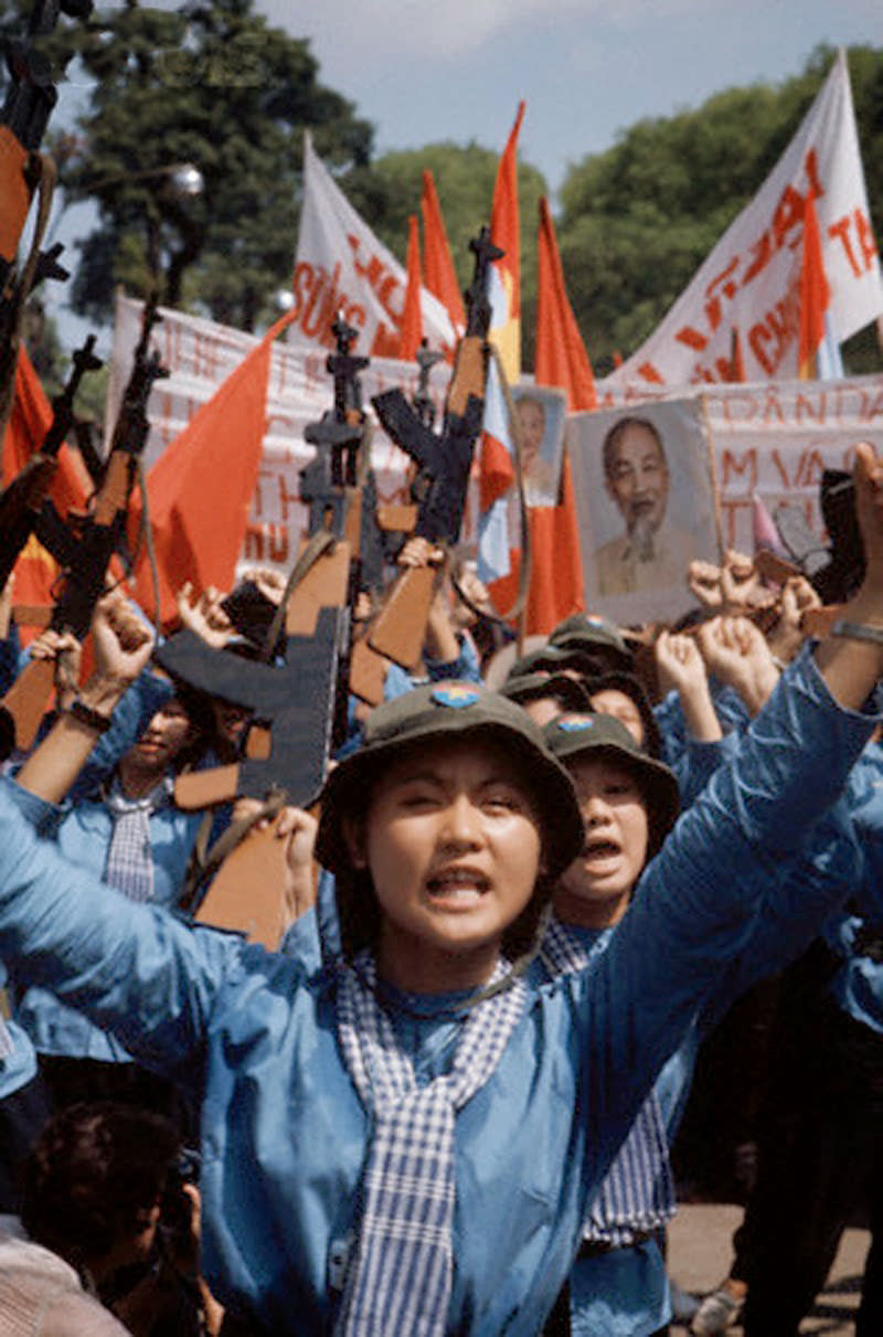 Female North Vietnamese troops enter Saigon carrying wooden rifles, red flags, and portrait of Ho Chi Minh. 30 Apr 1975, Saigon, South Vietnam