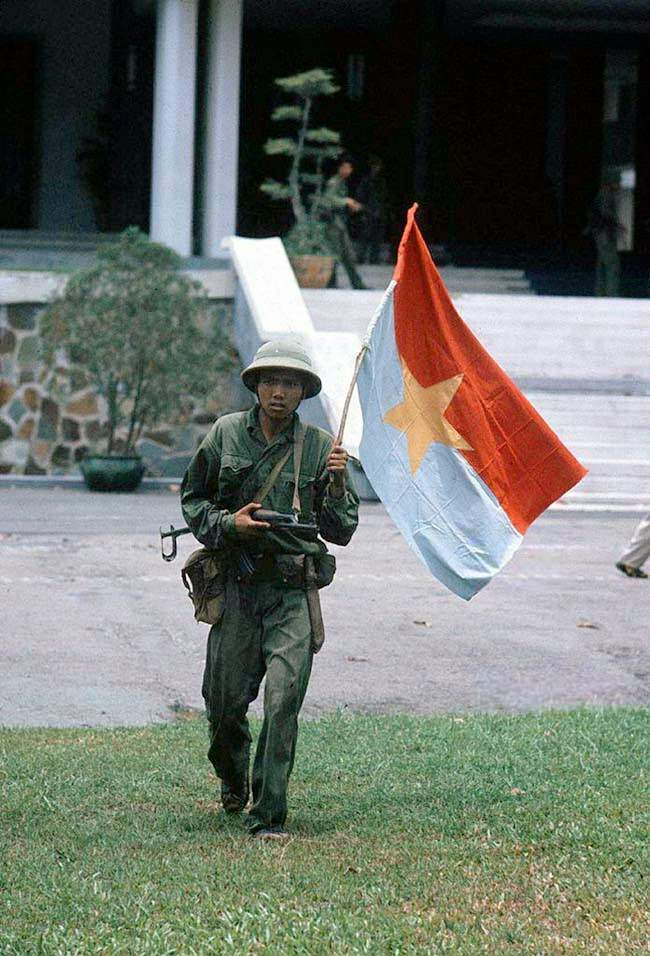 Taken of the presidential palace. North - Vietnamese officer holding a flag of the G.R.P. April 30, 1975.