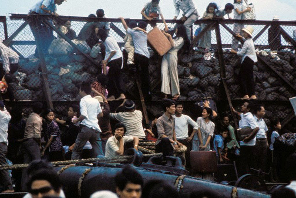 South Vietnamese clamber aboard barges in the port of Saigon in an attempt to escape from advancing North Vietnamese troops on the day of the Fall of Saigon that ended the Vietnam War