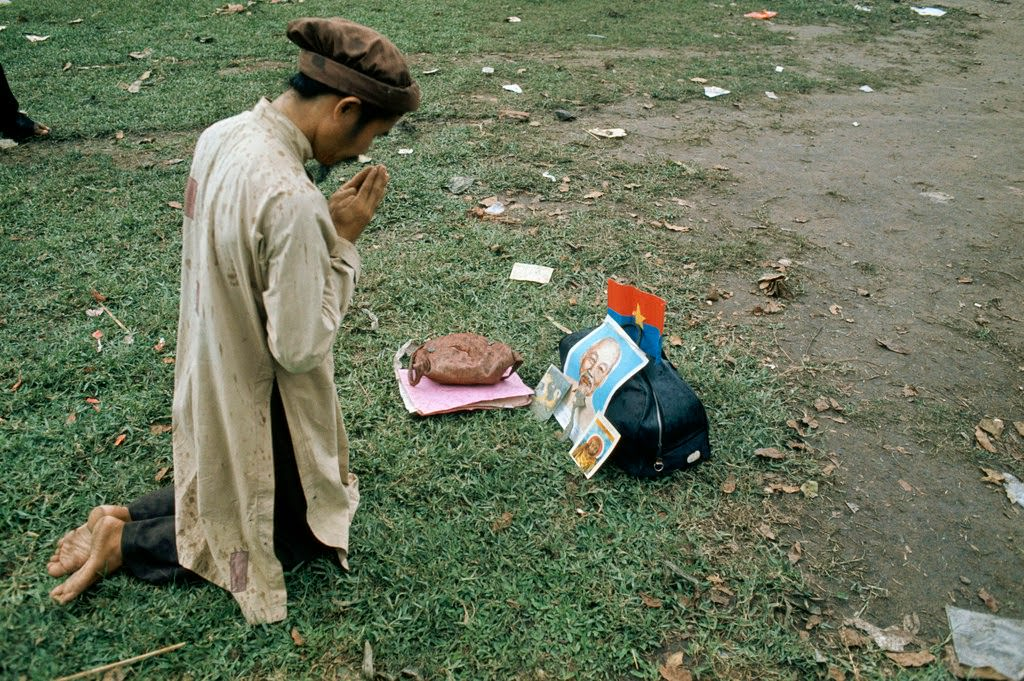 A Vietnamese man prays in front of a portrait of Ho Chi Minh after the Fall of Saigon.
