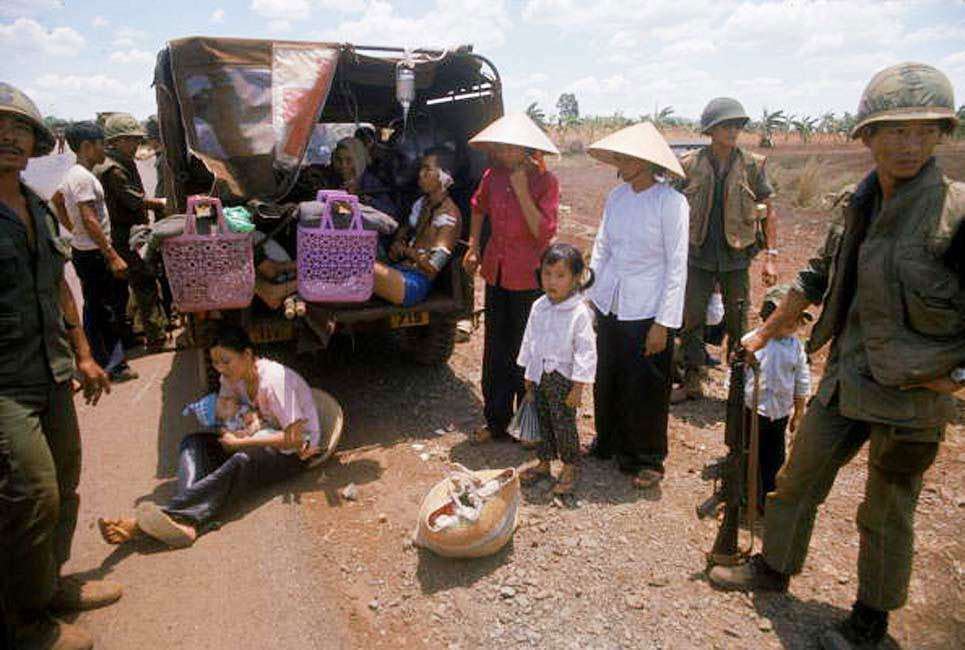 South Vietnamese citizens seeking to flee the country April 1975 are assisted by South Vietnamese troops.